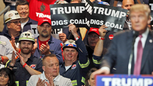 Coal miners wave signs at Trump's May 5 rally in Charleston, West Virginia.